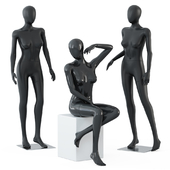 Two female mannequins stand and one sits on a white square stool 58